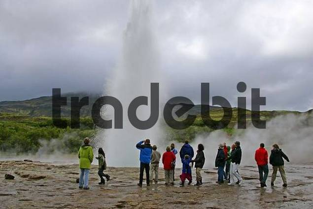 tourists looking at the geyser Strokkur in Iceland