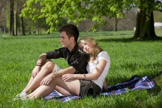 Young couple sitting on a picnic blanket under a tree in a park in spring