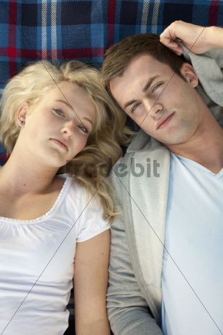 Young couple lying on a picnic blanket