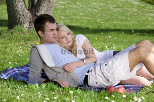 Young couple lying on a picnic blanket in a park, spring