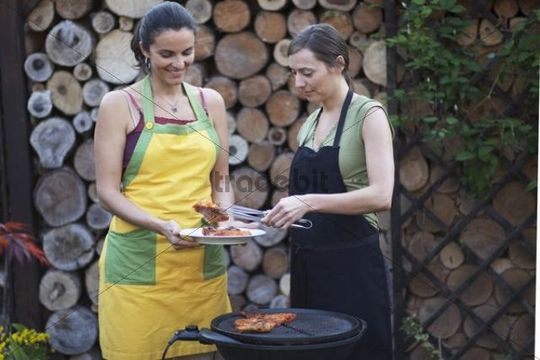 Two women barbecuing