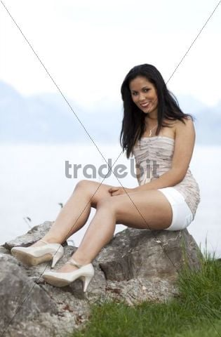 Young woman wearing white hot pants and high heels sitting on a rock, smiling