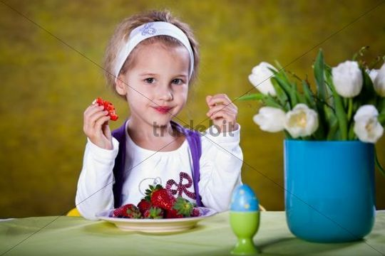 Little blonde girl eating strawberries at a table