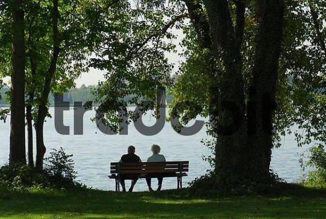old married couple sitting on a park bench at lake Chiemsee, Upper Bavaria, Bavaria, Germany