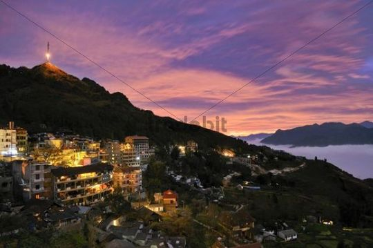 Lit houses, Sapa with Mt. Ham Rong and transmission tower, spectacular cloud mood, sea of clouds at sunset, Muong Hoa valley, Lao Cai province, northern Vietnam, Vietnam, Southeast Asia, Asia