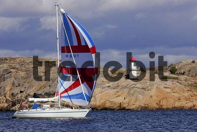 little lighthouse and norwegian sailing boat at the swedish Baltic Sea coast with granite rocks - Europe, Skandinavia, Sweden, Bohuslaen, near by Ramsvik, West coast, Baltic Sea coast