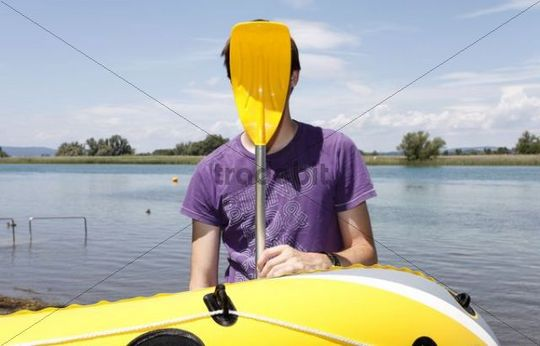 Young man holding paddle of rubber dinghy in front of his face, having fun boating, transition of Lake Constance into Seerhein river and Untersee lake, Taegerwilen, Switzerland, Europe