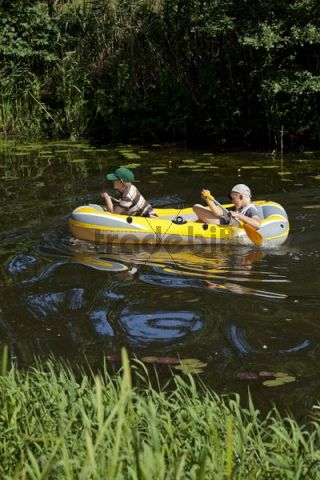 Two boys in a rubber boat in a river, Barum, Lower Saxony, Germany, Europe