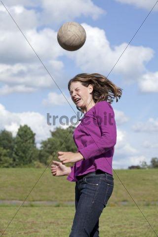 Girl playing football, heading ball