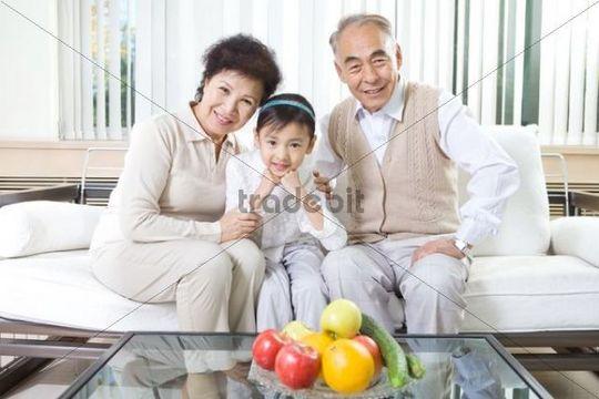 Grandparents and grandchild sitting on sofa, China, Asia
