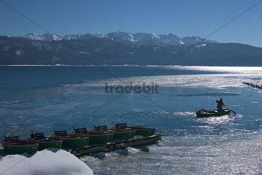 Fisherman breaking ice on Lake Walchen, Bavaria, Germany, Europe
