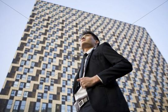 Low angle view of businessman standing in front of a high building, China, Asia