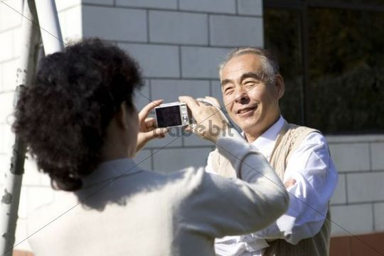Elderly Asian couple taking pictures in backyard, China, Asia