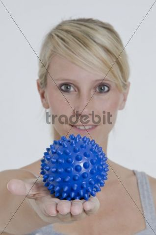 Young woman with her arm outstretched and holding a blue spiky massage ball in her hand