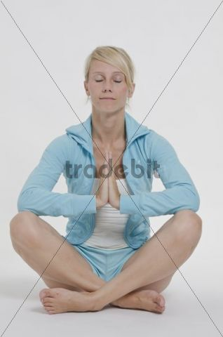 Young woman wearing sports clothing sitting cross-legged on the floor