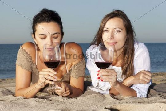 Two young women drinking wine on a beach