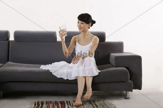 Young Asian woman sitting on sofa with a glass of water