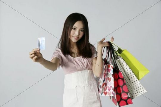 Young Asian woman with many shopping bags, holding a card