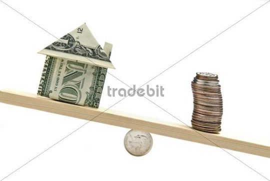 House-shaped folded dollar bill and coinstack on see-saw
