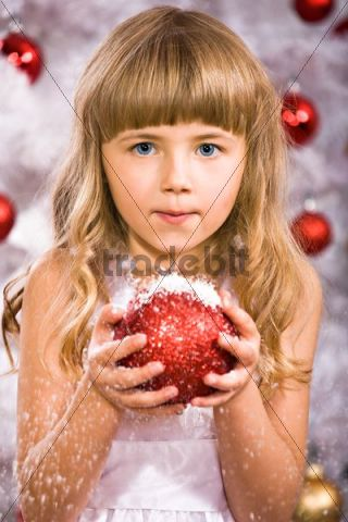 Young girl holding a Christmas bauble in front of a Christmas tree