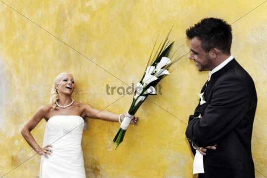 Wedding, laughing bride holding out the bridal bouquet towards the groom in front of a yellow wall