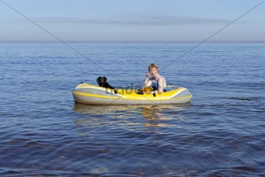 Woman with dog in a rubber boat, Kuehlungsborn-West, Mecklenburg-Western Pomerania, Germany, Europe