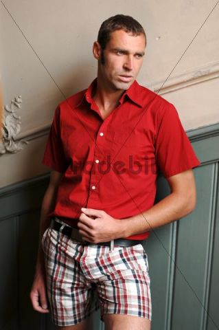 Man, 37 years, wearing a red shirt standing in a hallway