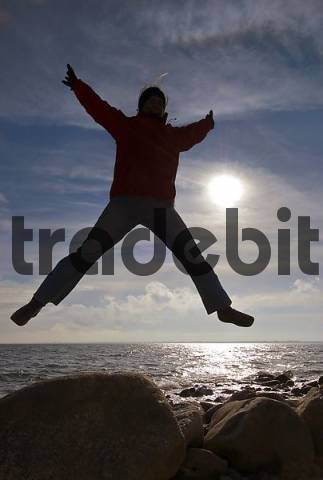 woman jumps into the air, Kiel Bay, Schleswig-Holstein, Germany
