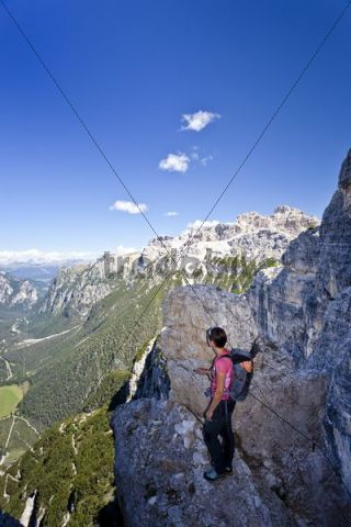 Female mountaineer during the ascent to Monte Piano, fixed rope route in Alta Pusteria Valley, Dolomites, Hoehlensteintal valley at back, South Tyrol, Italy, Europe