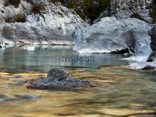 Boulders and rocks in the river bed of the golden coloured Soca river in Soca Valley near Bovec, Triglav National Park, Slovenia, Europe