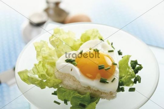 Toast with heart-shaped fried egg, salad leaves, chives