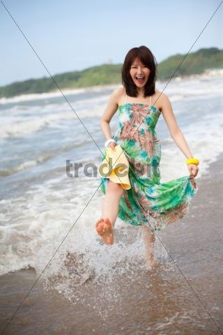 Young Asian woman laughing, playing at seaside