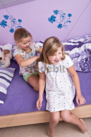 Two girls, sisters doing their hair after waking up