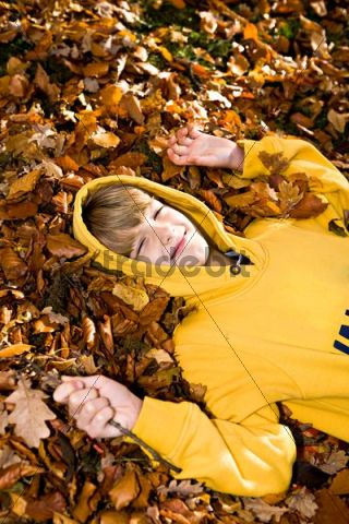 Boy lying amidst autumn leaves
