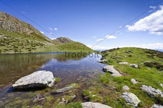 Lake below the summit of Mt Hochwart, during ascent to Mt Ultner Hochwart in Ultental valley, Mt Kornigl at back, Ulten in spring, South Tyrol, Italy, Europe