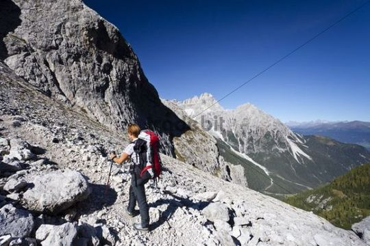 Hiker during the ascent to Alpinisteig climbing route through Fischleintal Belly above Talschlusshuette, hut, Mt Dreischusterspitze at back, Alta Val Pusteria, Sesto, Dolomites, South Tyrol, Italy