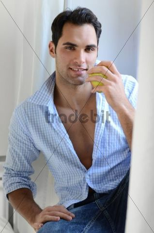 Young man sitting on a window sill eating an apple
