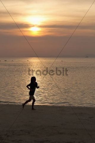 Woman running on a beach at sunset, Hat Tham Phra Nang beach, Krabi, Thailand, Asia