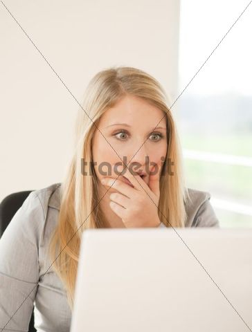 Young woman working on computer, puzzled