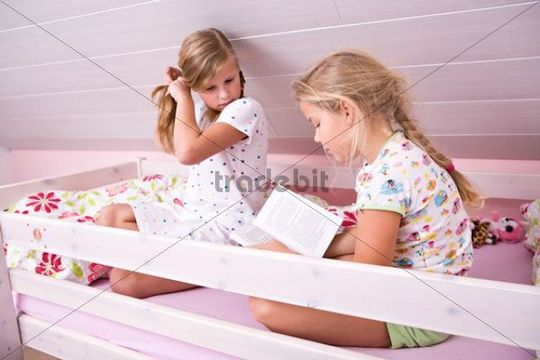 Sisters reading a book in the bed
