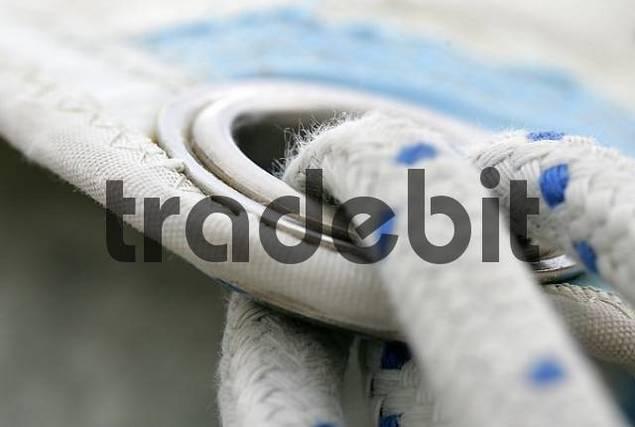 Sailing rope sticks through an eyelet of a sail