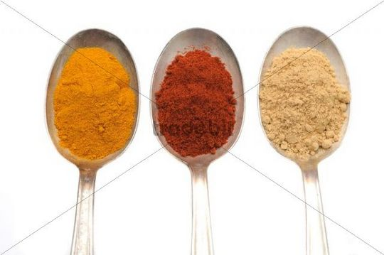 Spices on old spooks, curry, paprika and ginger powder