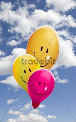 Three coloured smiley balloons against a blue sky with clouds