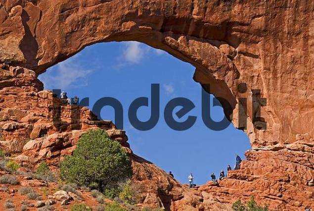 tourists enjoy natural arch North Window in Arches National Park Utah USA