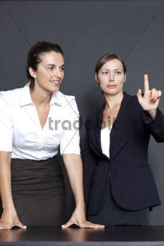 Two women at virtual screen, black backdrop