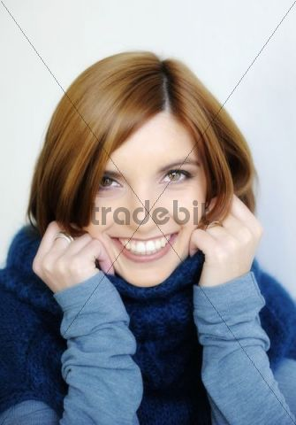 Young smiling woman wearing a turtleneck sweater, portrait
