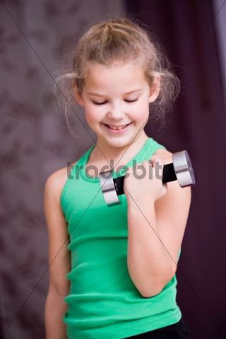Girl, 8, exercising with a small dumbbell