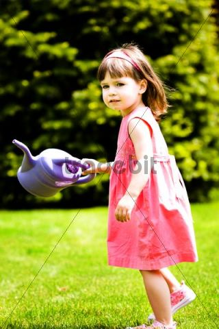 Girl, 3 years, with a watering-can in the garden