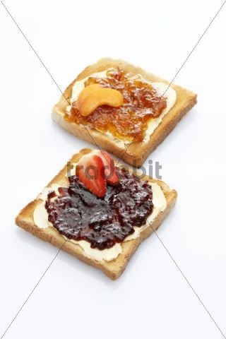 Two slices of toast, toasted slices of bread, strawberry jam and apricot jam