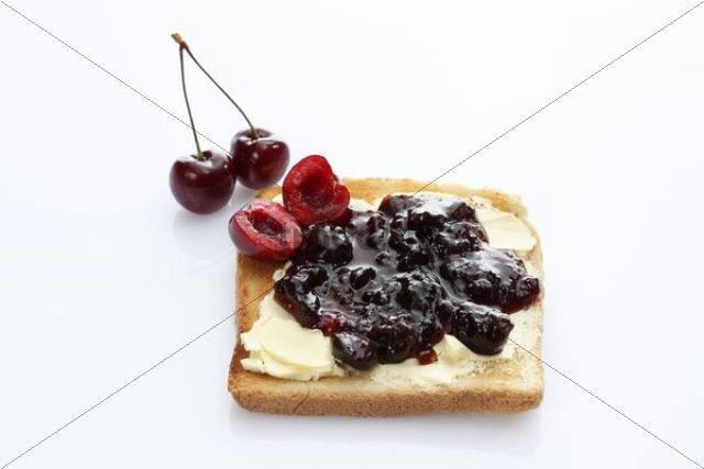 Slice of toast, toasted slice of bread, with cherry jam and chrries